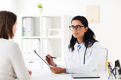 medicine, healthcare and people concept - doctor with clipboard and woman patient at hospital | Global Consulting Services Firm
